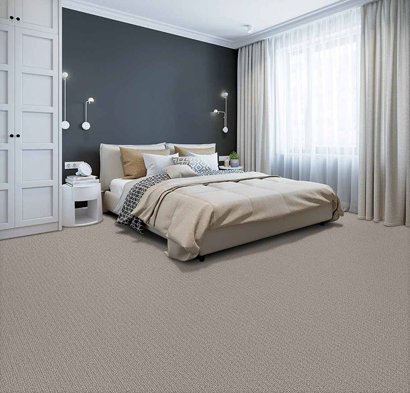 Modern 2020 bedroom designed with a minimalism technique and neutral colors to include a slate grey wall and beige carpet.
